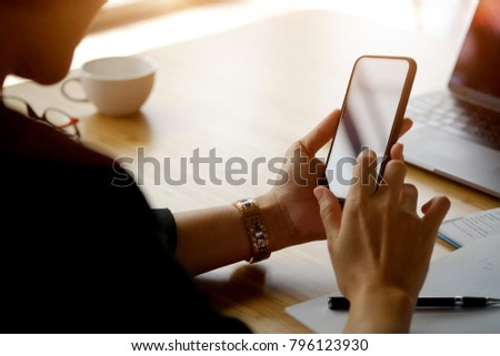 Closeup shot of an unidentifiable woman using a mobile phone at office