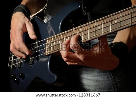 closeup shot of bass guitar in hands of musician