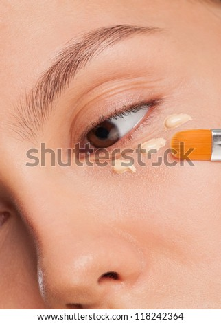 Closeup shot of beautiful young woman applying foundation on her face