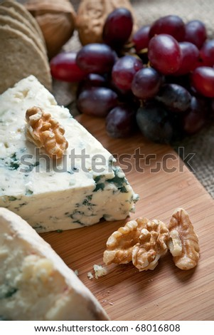 Closeup shot of blue cheese with walnuts and grapes