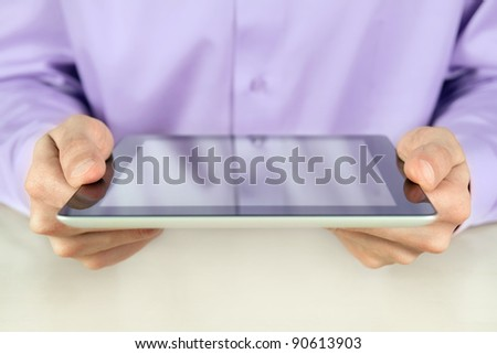 Closeup shot of businessman hands are holding contemporary generic tablet pc. Shallow depth of field on fingers.