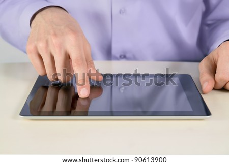 Closeup shot of businessman hands are touching on contemporary generic tablet pc. Shallow depth of field on finger.