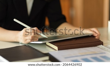 Closeup shot of businesswoman using stylus pen to write on touchpad, working on digital tablet computer.