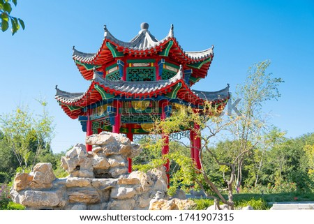 closeup shot of china style architecture pavilion with upturned eaves gray roof and painting in the  garden and stone sculpture nice place for family rest, own garden design, tourism, meditation