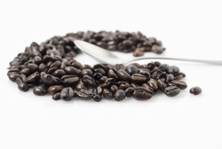 Closeup shot of coffee beans against white background with teaspoon