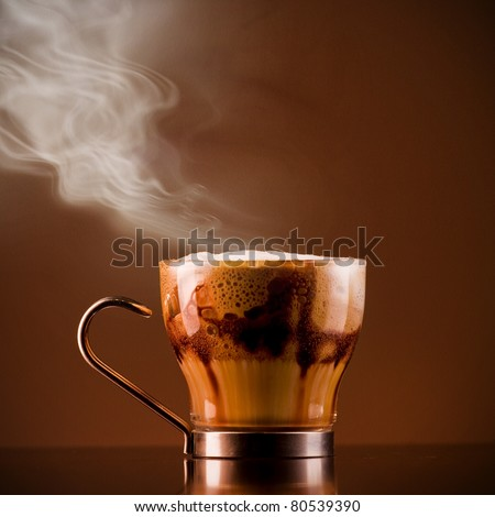 Closeup shot of Delicious smoking hot coffee drink macchiato, espresso with steamy milk and froth and added chocolate syrup for layered effect. Served on a bar in a glass cup. Textured background