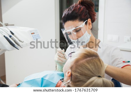 Closeup shot of dentist in protection mask working with tooth cavity and plague. Patient on stomatology chair repair aching teeth. Stomatologist and patient at clinic office. Toothcare concept Foto stock ©