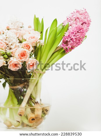 Closeup shot of different flowers standing in glass vase