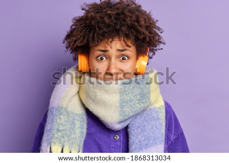 Closeup shot of displeased African American female shivers from cold wears warm scarf around neck spends much time outside during winter time listens audio track via headphones isolated on purple wall Stock photo ©