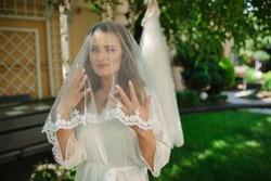 Closeup shot of elegant, brunette bride in vintage white dress posing under veil closeup. Bride portrait wedding makeup and hairstyle with diamond crown, fashion bride. Beautiful bride in veil