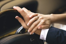 Closeup shot of elegant woman holding hand on men hand while he drives a car