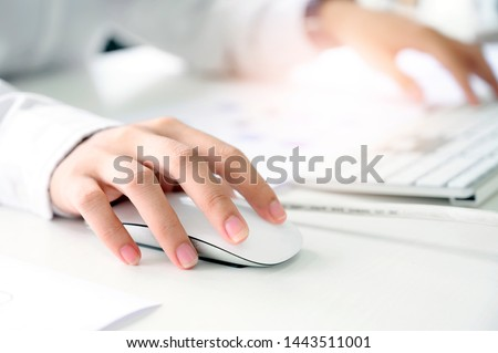 Photo of  Closeup shot of female hand holding mouse and working with desktop computer while sitting at office desk.