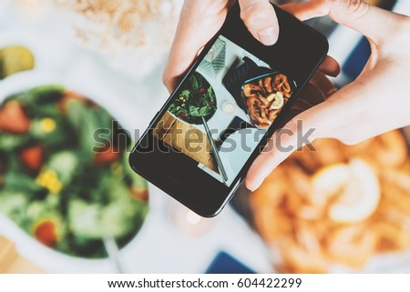 Closeup shot of female hands holding smartphone and taking a photo, top view of hipster girl taking a picture of food by smartphone