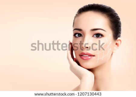 Closeup shot of female pretty face with white arrows on skin for cosmetic medical procedures, pastel background. Skin care concept