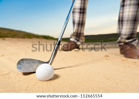closeup shot of golf ball with golf club right before tee off from bunker