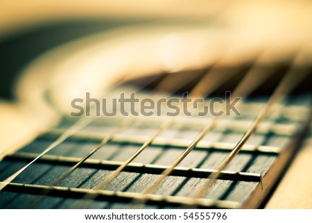 closeup shot of guitar and strings with shallow depth of field