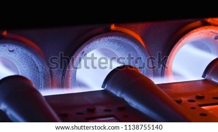 Closeup Shot Of Home Furnace Burner Ignited With Crimson Blue Flame ストックフォト ©