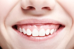 Closeup shot of human female face. Woman with pink lips and healthy dentes. Girl is smiling
