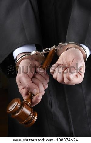 closeup shot of judge holding gavel in handcuffs