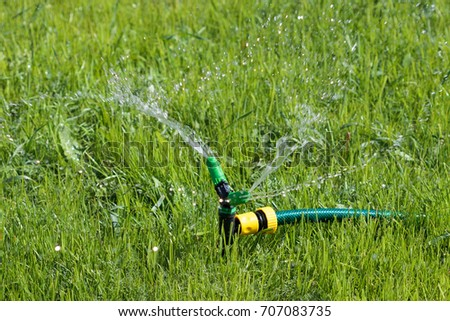 Closeup shot of lawn sprinkler spaying water over green grass field. Irrigation system #707083735