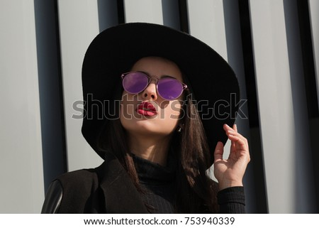 Closeup shot of luxury brunette woman with bright makeup and shiny hair wears hat and sunglasses
