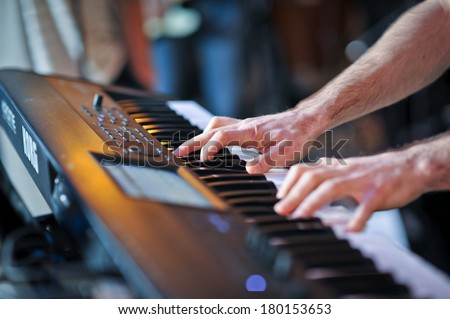 closeup shot of male hands playing the piano .Human hands playing the piano on the party . Man playing the synthesizer keyboard