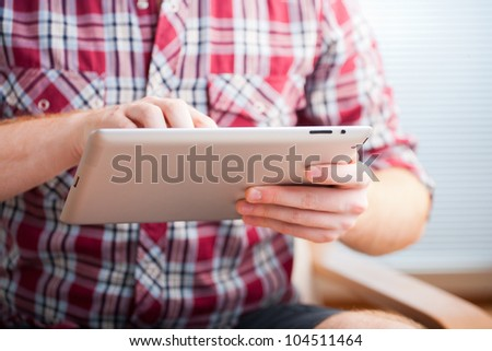 Closeup shot of male hands using a tablet