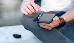 Closeup shot of man hands holding blank screen smartphone while sitting outdoors, shallow depth of field.