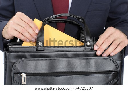 Closeup shot of man removing envelope from briefcase