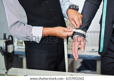 Shutterstock Closeup shot of old-fashioned tailor taking wrist measurements from client in small atelier studio to make custom classic suit with jacket