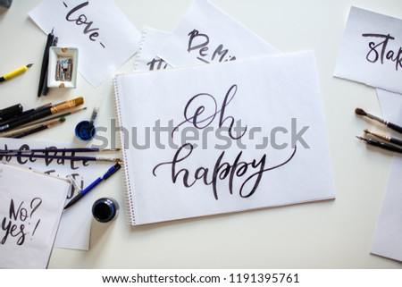 Closeup shot of papers with Oh happy words and notepad with calligraphic handwriting #1191395761