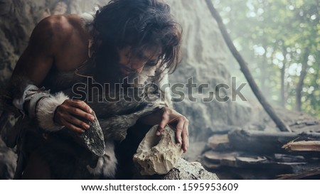 Closeup Shot of Primeval Caveman in Animal Skin Hits Rock with Sharp Stone, Makes First Primitive Tool for Hunting Animal Prey. Neanderthal Using Flint Rock. Dawn of Human Civilization.