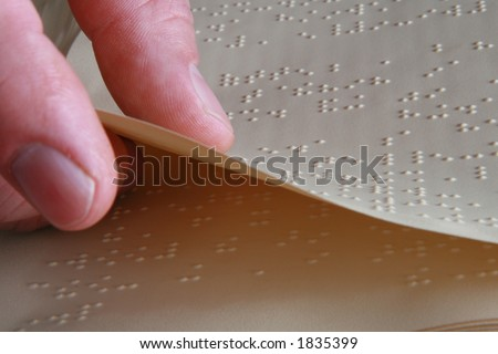 closeup shot of someone turning a Braille book page