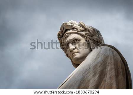 Closeup shot of the famous white marble monument of Dante Alighieri by  Enrico Pazzi in Piazza Santa Croce, next to Basilica of Santa Croce, Florence, Italy on a moody sky background