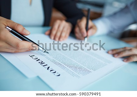 Closeup shot of two business partners signing contract at meeting: woman pointing and man putting signature below text