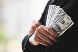 Closeup shot of United States of America hundred dollars banknotes currency in successful rich wealth male businessman cross arms wears black formal suit hand with blurred background.