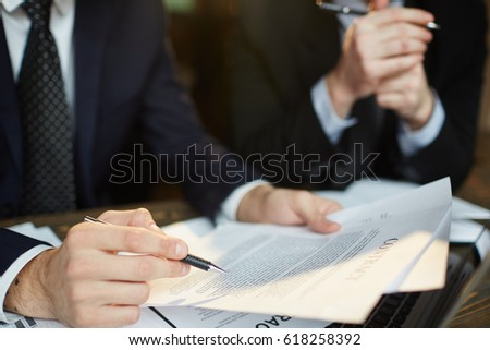 Closeup shot of unrecognizable businessman reading contract documentation at meeting with financial partner