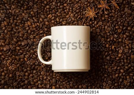 Closeup shot of white mug against coffee beans with anise stars lying like steam