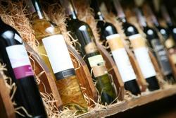 Closeup shot of wine shelf. Bottles lay over straw. Wine cellar.