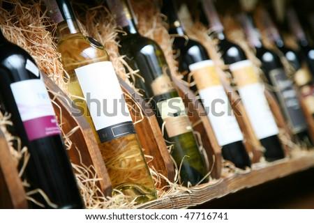 Closeup shot of wine shelf. Bottles lay over straw. Wine cellar. Stock photo ©