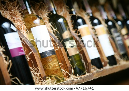 Closeup shot of wineshelf. Bottles lay over straw.