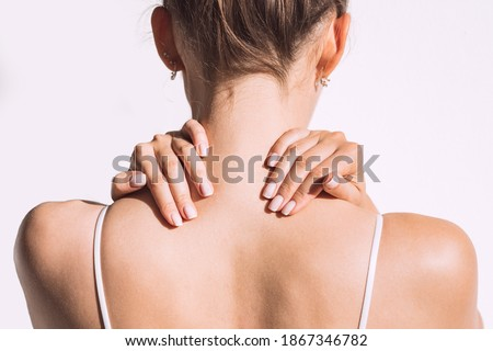 Closeup shot of woman from back having neck or shoulder pain. Injury or muscle spasm. Back and spine disease. Female massaging her neck. Health care and medical concept