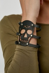 Closeup shot of woman's hand, wearing olive sweater. The lady is touching her forearm with leather slave bracelet with thin straps on her hand. The accessory is adorned with silver ring and studs.