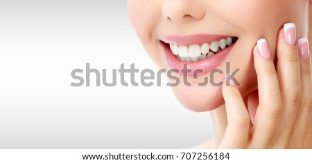 Closeup shot of woman's toothy smile against a grey background with copyspace
