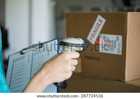 Closeup shot of worker scanning box with barcode reader. Reading and Scanning labels on the boxes with bluetooth barcode scanner in a warehouse.