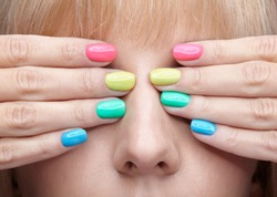 Closeup shot of young blonde woman with fun  varicoloured finger nails manicure.