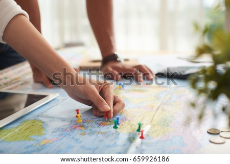 Closeup shot of young couple putting pins to map, marking travelling destinations and planning vacation budget #659926186