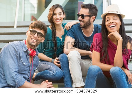 Closeup shot of young friends sitting on staircase having fun. Happy girls and guys smiling and looking at camera. Young men and young women stay together. #334374329
