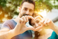 Closeup shot of young man and woman making heart shape with hand. Loving couple making heart shape with hands outdoor. Female and male hands making up heart shape.