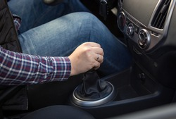 Closeup shot of young man shifting manual gearbox in car